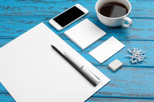 Top view of paper, business cards, pad, pens and coffee