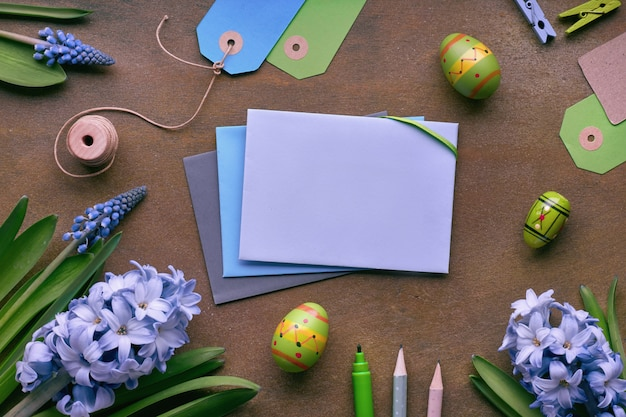 Top view of paper cards with copy-space, blue hyacinth flowers and easter eggs on dark background, text
