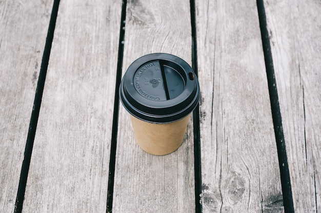 Top view of paper coffee cup on wood