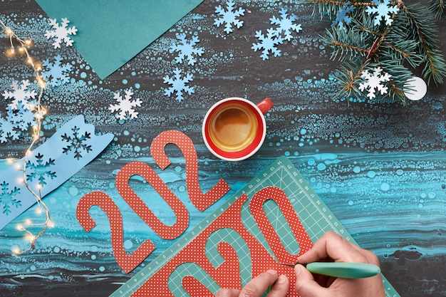 Top view, paper craft with hand cutting number 2020, cup of coffee and christmas decorations