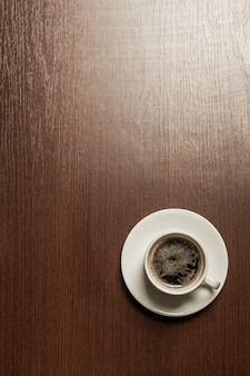 Top view of a paper cup of black coffee on wooden surface table