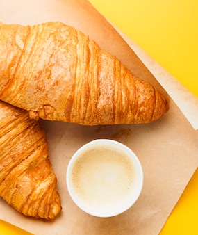 Top view of paper cup of coffee and two croissants on craft paper