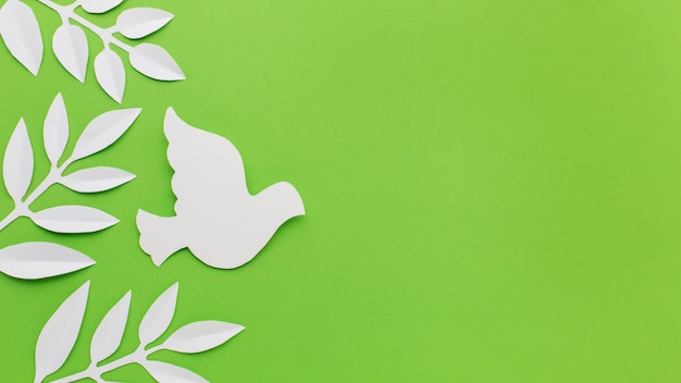 Top view of paper dove and leaves with copy space