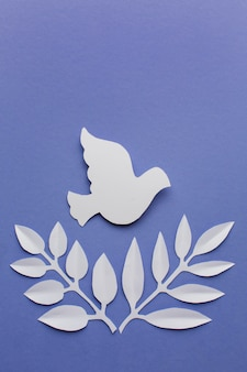 Top view of paper dove with leaves and copy space