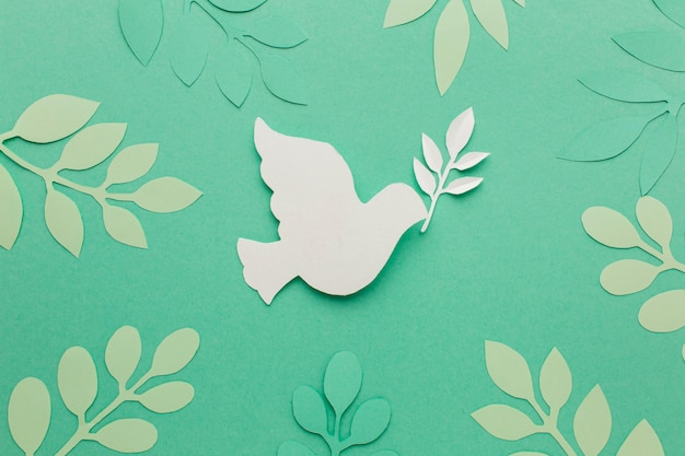 Top view of paper dove with leaves