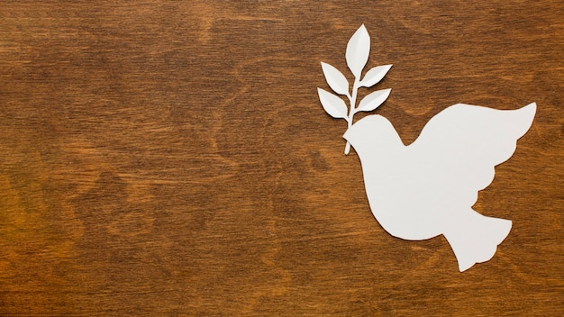 Top view of paper dove on wooden surface with copy space