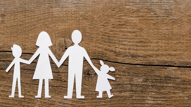 Top view paper family composition on wooden background with copy space