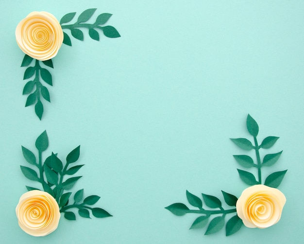 Top view paper flowers and leaves on blue background