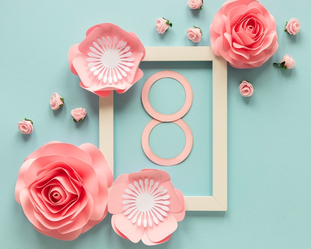 Top view of paper flowers with frame and date for women's day