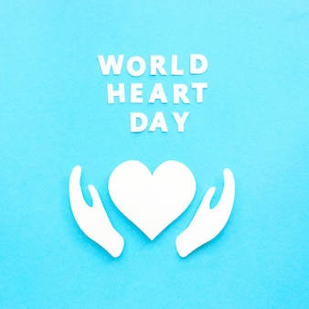 Top view of paper heart and hands for world heart day