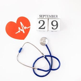 Vista dall'alto del cuore di carta con data e stetoscopio