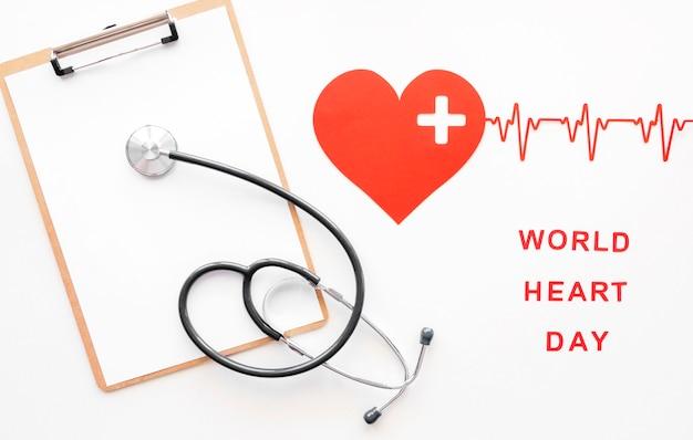 Vista dall'alto del cuore di carta con lo stetoscopio e il pad