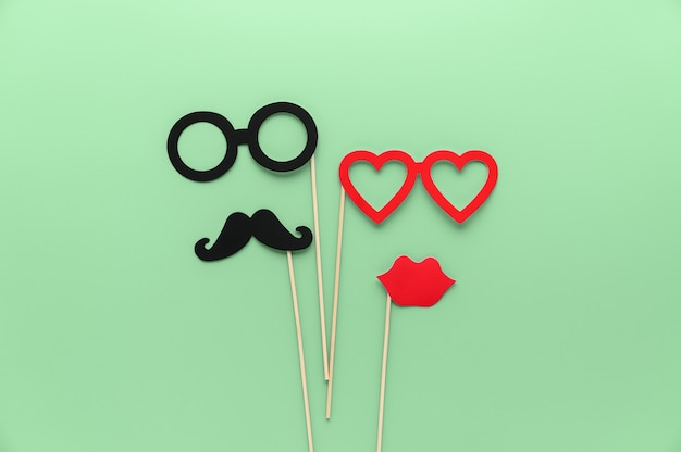 Top view paper male mustache, female lips and glasses on green ash