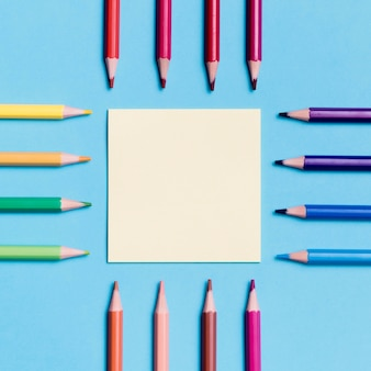 Top view paper note surrounded by colourful pencils