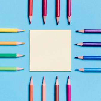 Вид сверху бумажная записка в окружении разноцветных карандашей