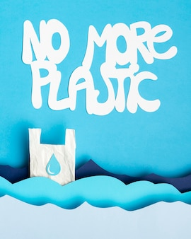 Top view of paper ocean waves with plastic bag and message