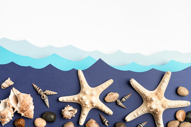 Top view of paper ocean waves with starfish and sea shells