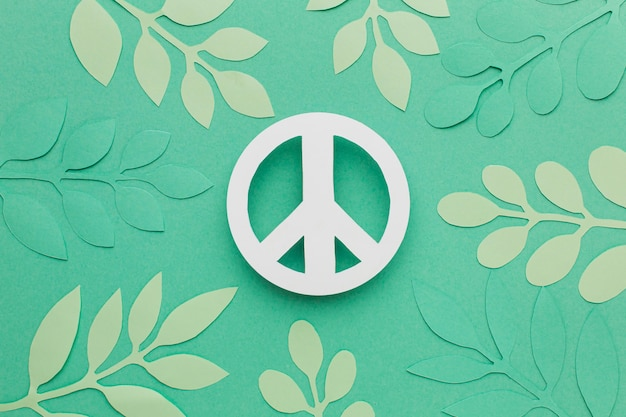 Top view of paper peace sign with leaves