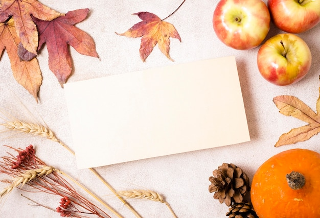 Top view of paper with apples and autumn leaves