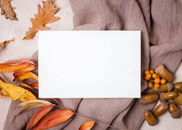 Top view of paper with autumn leaves and acorns