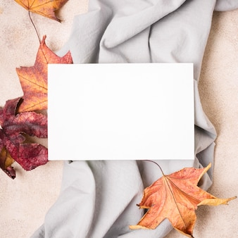 Top view of paper with fabric and autumn leaves