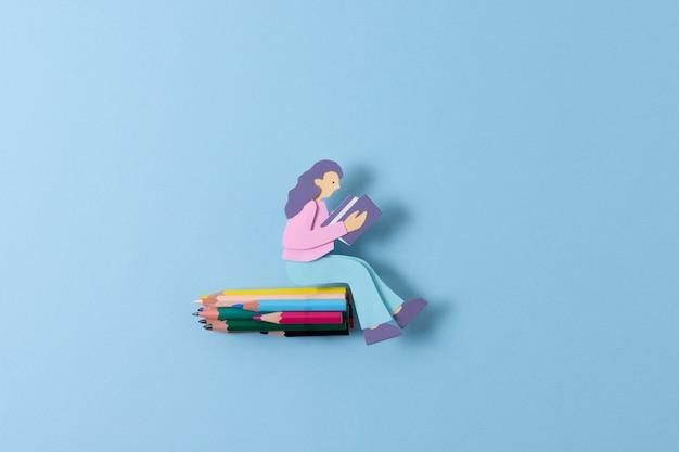 Donna di carta vista dall'alto seduta sui pastelli
