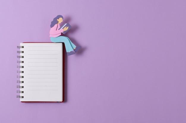 Вид сверху бумажная женщина, сидящая на ноутбуке
