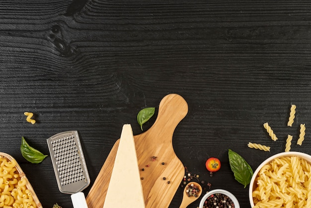 Top view of parmesan and pasta on wooden table
