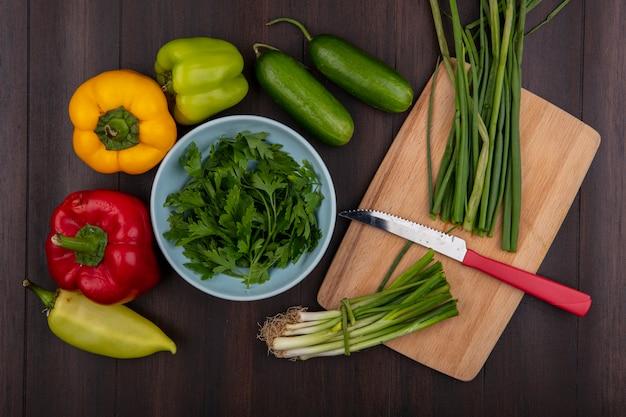 Vista dall'alto prezzemolo in una ciotola con cetrioli peperoni e cipolle verdi su un tagliere con un coltello su uno sfondo di legno