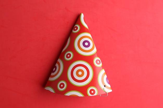 Vista dall'alto di un cappello da festa isolato su uno sfondo rosso