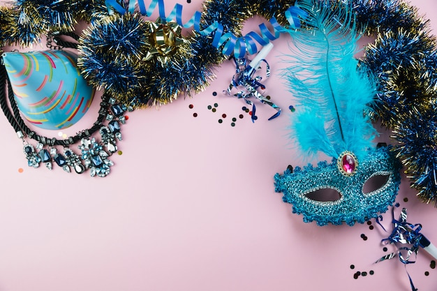 Top view of party hat; tinsel; necklace with confetti and blue masquerade carnival feather mask