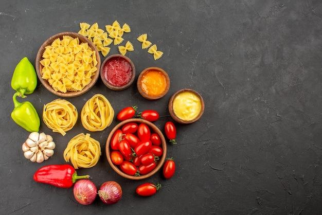 Вид сверху макароны и перец, тарелки с макаронами и помидорами, красный и зеленый перец, лук, чеснок, три вида соусов на столе