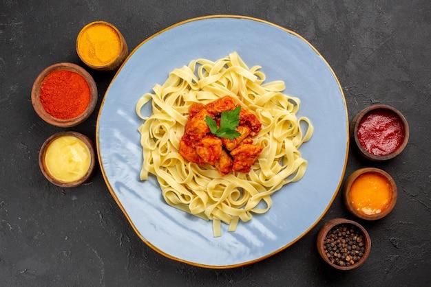 어두운 탁자에 있는 5가지 다채로운 소스 그릇 사이에 그레이비 허브와 고기를 넣은 파스타와 소스 파스타 접시