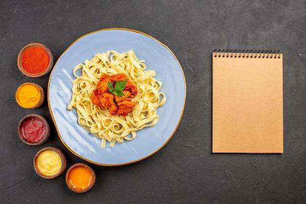 어두운 탁자에 있는 크림 공책 옆에 그레이비 허브와 고기를 곁들인 5가지 다채로운 소스와 파스타의 탑 뷰 파스타와 소스 그릇