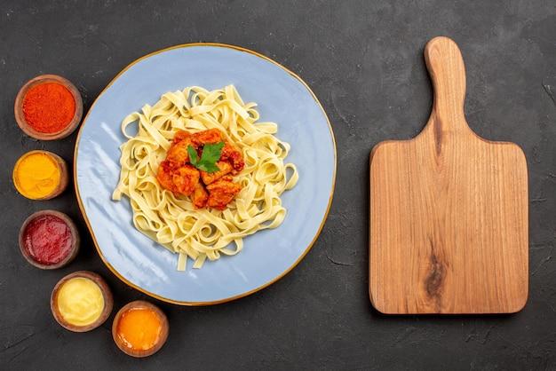 탑 뷰 파스타와 소스 파스타 그레이비와 접시에 있는 식욕을 돋우는 고기, 그리고 테이블 위에 있는 도마 옆에 있는 5가지 다른 소스