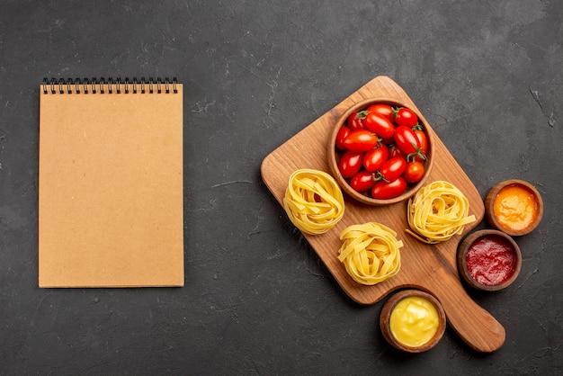 Вид сверху макароны и соусы помидоры и макароны на разделочной доске и разные соусы рядом с блокнотом с кремом на столе