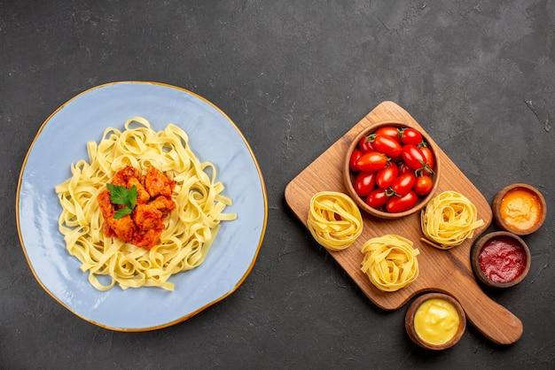 Вид сверху макароны и соусы помидоры и макароны на разделочной доске и разные соусы рядом с тарелкой аппетитных макарон с мясом и подливкой на темной поверхности