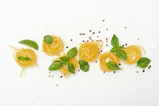 Top view of pasta and basil on plain background
