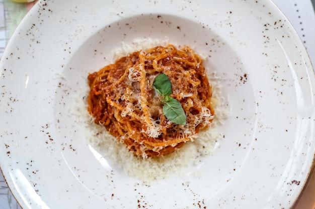 Вид сверху паста болоньезе с тертым сыром в тарелке