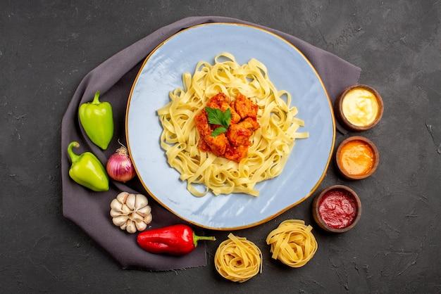 Vista dall'alto ciotole di pasta di salse pasta colorata palla pepe aglio cipolla accanto alla pasta appetitosa con carne ed erbe sulla tovaglia