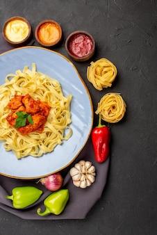 Vista dall'alto ciotole di pasta di salse pasta colorata palla pepe aglio cipolla accanto al piatto di pasta con carne sulla tovaglia