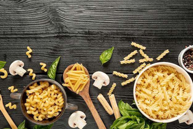 Top view of pasta and bowls on wooden table