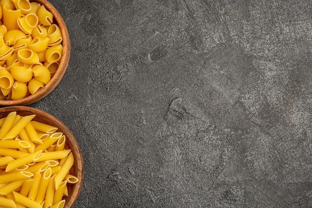 Vista dall'alto dei prodotti grezzi della composizione della pasta all'interno dei piatti su grigio nero