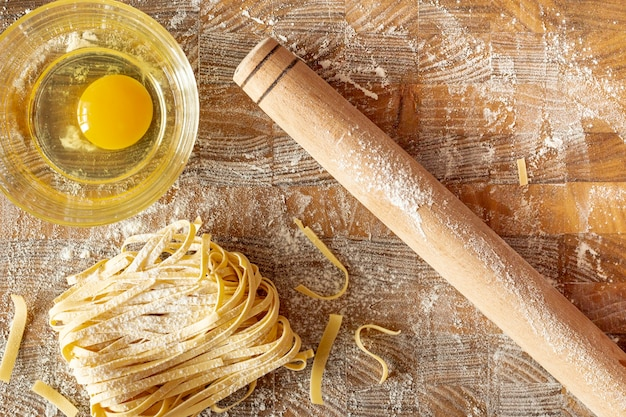 Top view of pasta and egg on wooden background