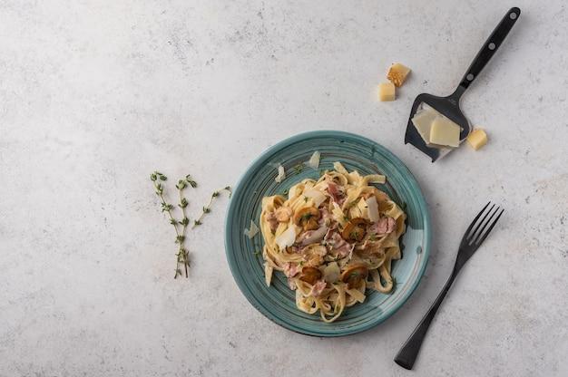 Вид сверху паста феттучини с грибами, беконом и сыром пармезан в белой тарелке