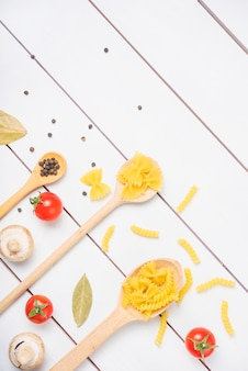Top view of pasta ingredients with spices and vegetables on white plank table