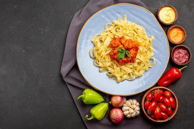 Вид сверху макароны на скатерти тарелка аппетитных макарон рядом с миской помидоров и красочных соусов чеснок, луковый шарик, перец на фиолетовой скатерти на столе