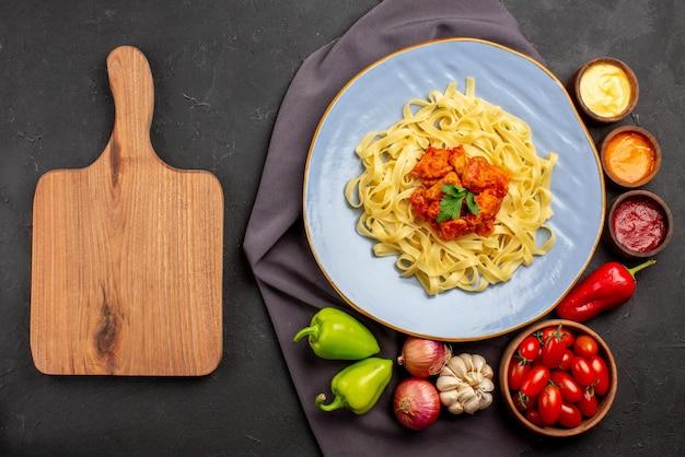 식탁에 있는 보라색 식탁보에 토마토와 다채로운 소스 마늘 양파 볼 후추로 구성된 식욕을 돋우는 파스타 그릇 옆에 있는 식탁보 나무 커팅 보드에 있는 상위 뷰 파스타