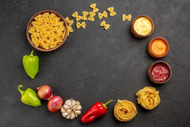 그릇에 다채로운 소스 녹색 및 빨간색 볼 후추 마늘 양파의 상위 뷰 파스타 파스타는 검은 테이블에 원에 배치됩니다