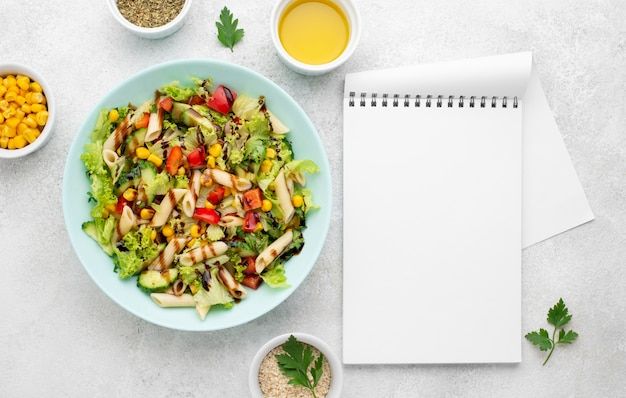 Top view pasta salad with balsamic vinegar and blank notebook